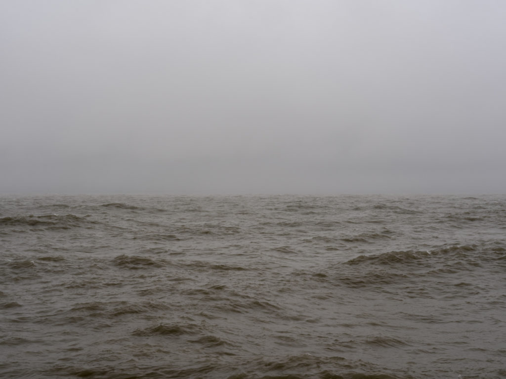 turbulent lake in winter with brown water and heavy cloud cover
