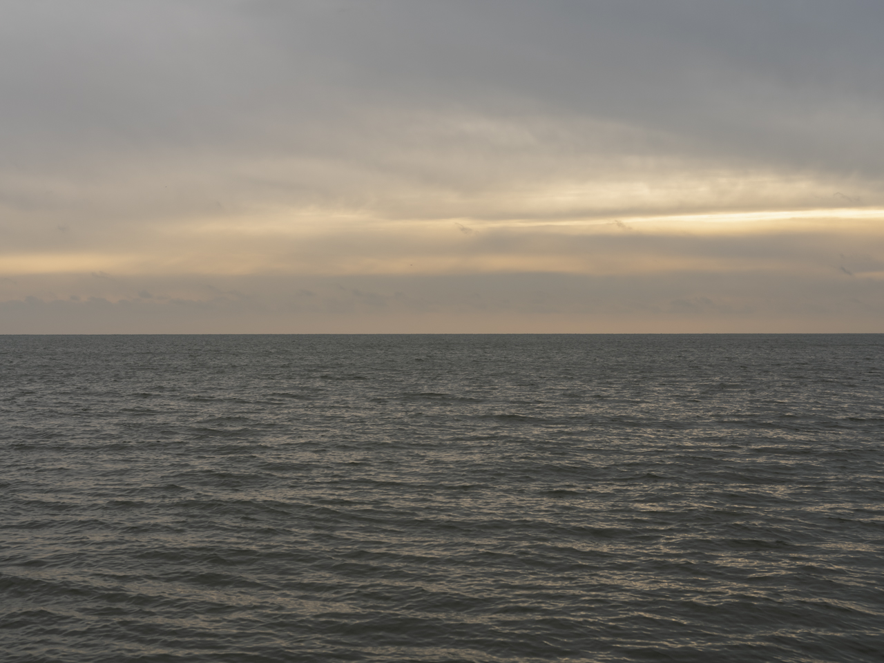 yellow and grays fill a cloudy sky where the sun is pushing through from behind, but not fully being shown, the lake waters are a strange gray brown and green color
