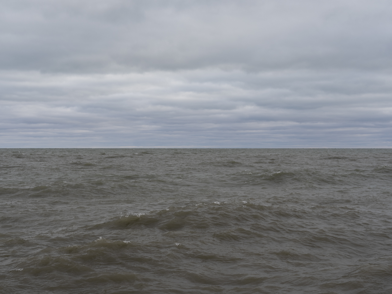 the lake is starting to churn with waves forming and heavy clouds in the sky overhead