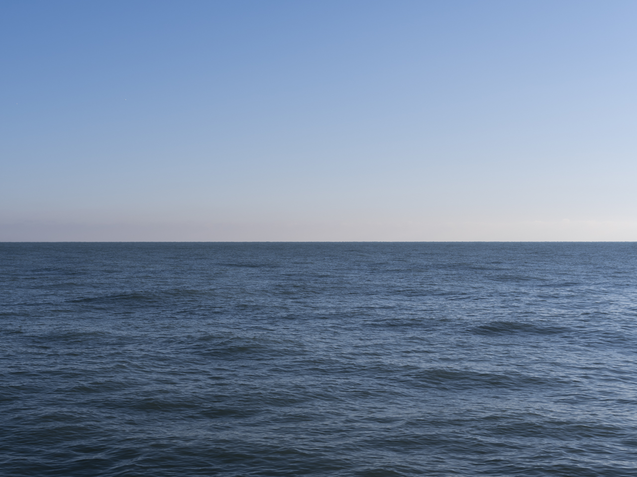 a clear blue sky with pastel horizon on Lake Michigan