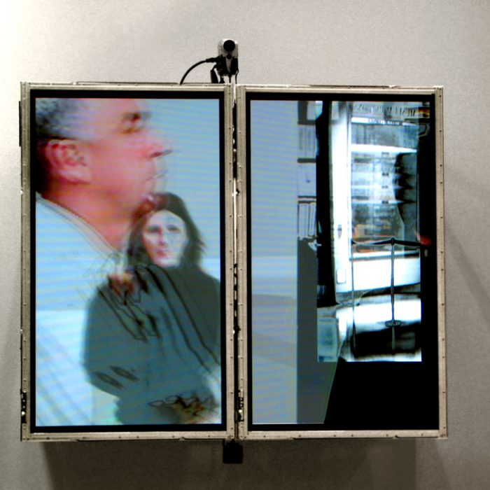 two tv screens, stripped of their frames are mounted vertically on a wall with a video camera, video from Lincoln Schatz's artwork is displayed on the screens