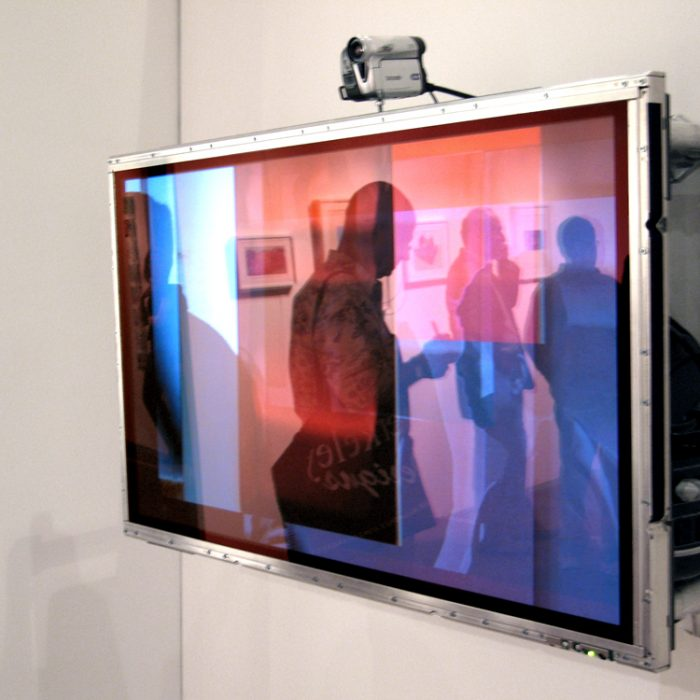 a horizonal screen is hung on a wall with a video camera above it with generative video layering video footage of viewers
