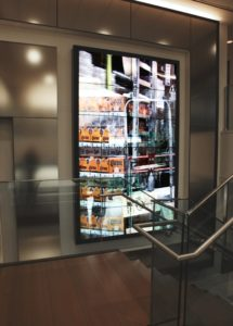 an installation of a video wall at Reyes Holdings by artist Lincoln Schatz with footage of a distribution network