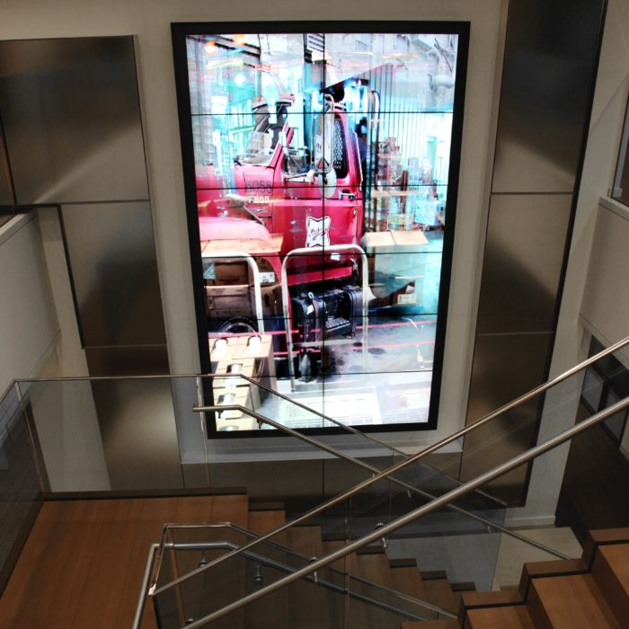 an installation of a video wall by artist Lincoln Schatz with footage of a distribution network