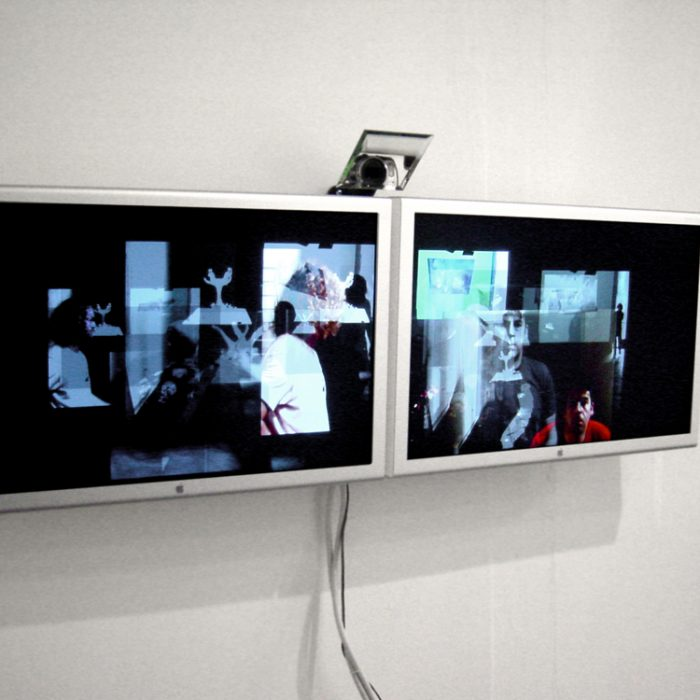 two computer screens are mounted to a wall with a mirror angled above them with a camera recording the room and displaying the room in many video layers on the tv screens