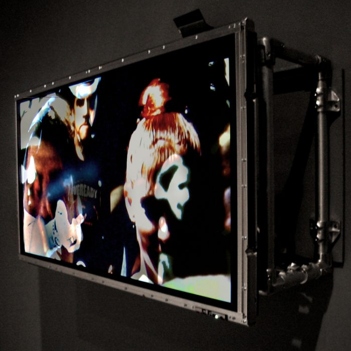 a TV screen, 16:9 in ratio has had its housing removed and it has been mounted to a black wall, multiple layers of video are superimposed on one another and shown on the screen of the artwork Slip by Lincoln Schatz