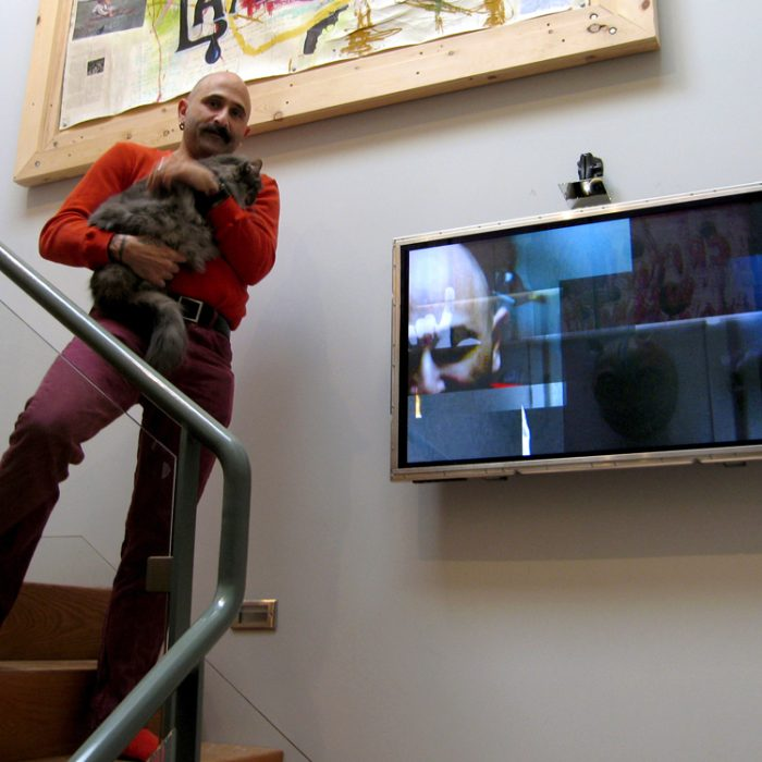 A many stands on a set of red stairs, wearing all red and holding a cat, beside him is a screen and camera for Lincoln Schatz's artwork Slip