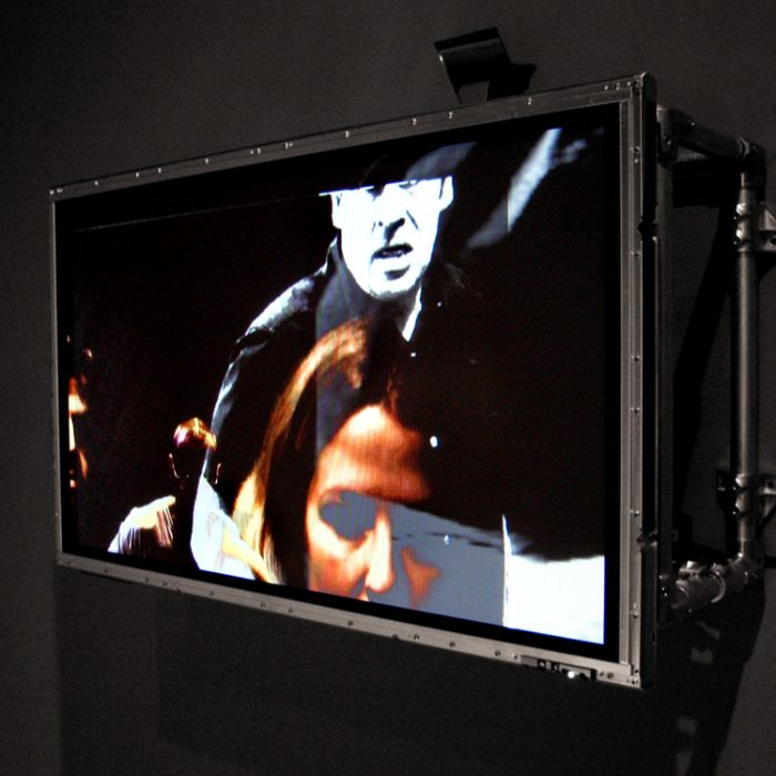 a TV screen, 16:9 in ratio has had its housing removed and it has been mounted to a black wall, multiple layers of video are superimposed on one another and shown on the screen