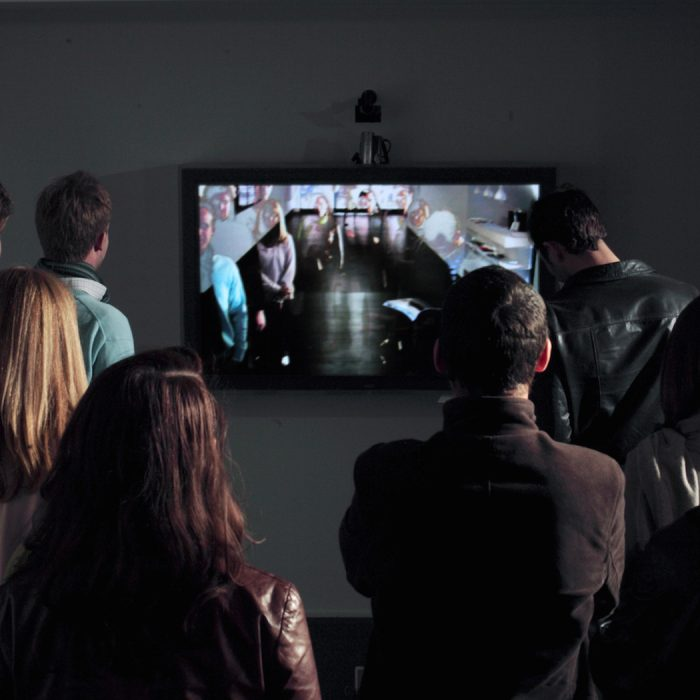 a television screen is mounted to the wall and an audience of people stand in front of it looking at recorded videos of themselves being played over one another with varying transparencies