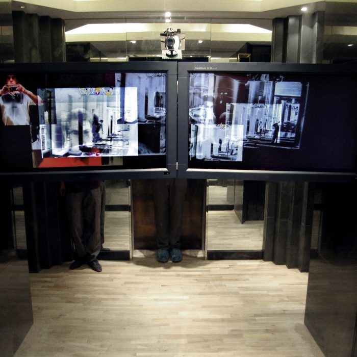 two video screens are mounted horizontally in a dark and small room with mirrors, a camera records the space in front of the screens and many layers of old video recordings display on the screens
