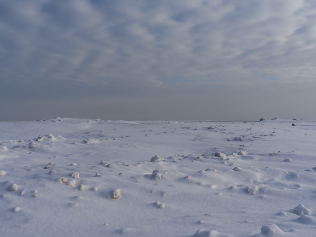 a frozen morning with low light, ice and snow cover Lake Michigan