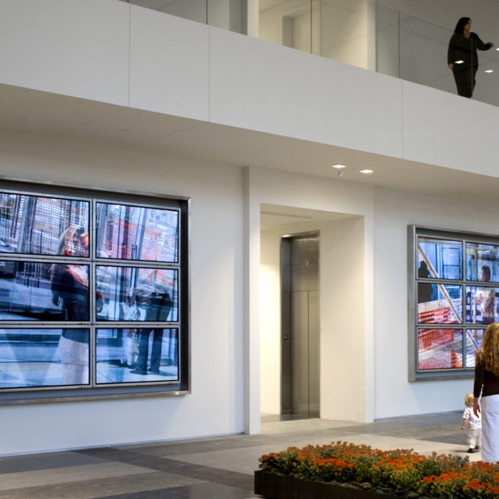 people stand in front of a video artwork called From Here, comprised of 2 banks of 6 televesion screens flanking the elevator core of a contemporary building lobby