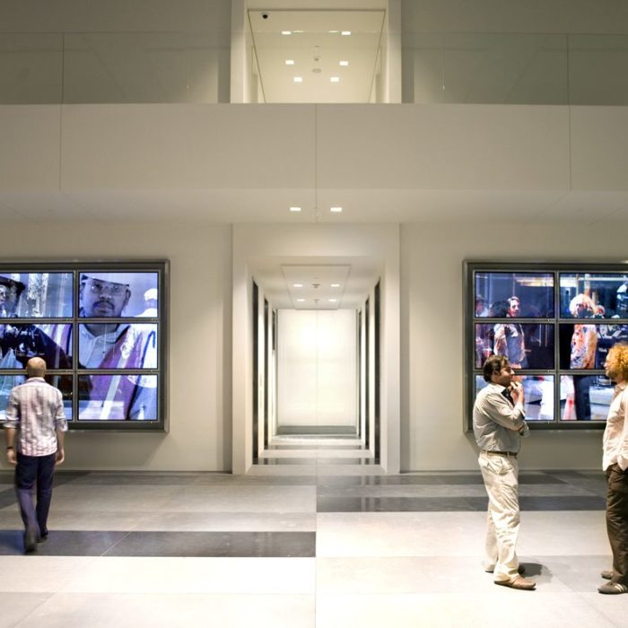 3 men stand in front of a video artwork called From Here, comprised of 2 banks of 6 televesion screens flanking the elevator core of a contemporary building lobby