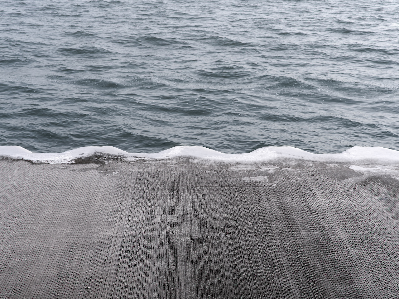a sliver of ice forms along the edge of the wet concrete that sits at waters edge