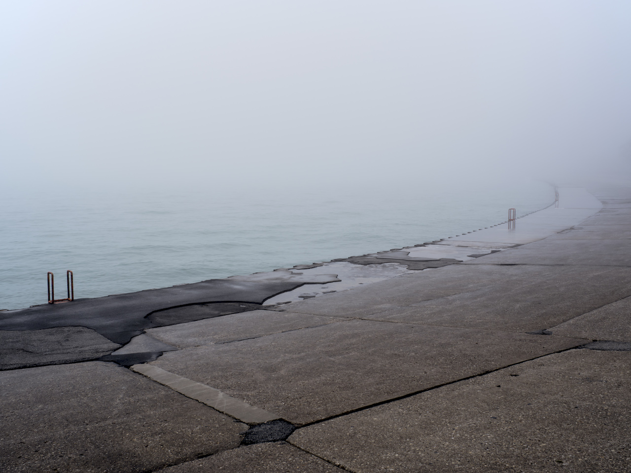 a heavy foggy day on Lake Michigan with wet concrete breaking up