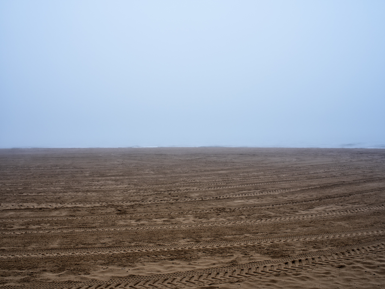 a foggy day with wet sands on Lake Michigan, with tracks of various machines and people