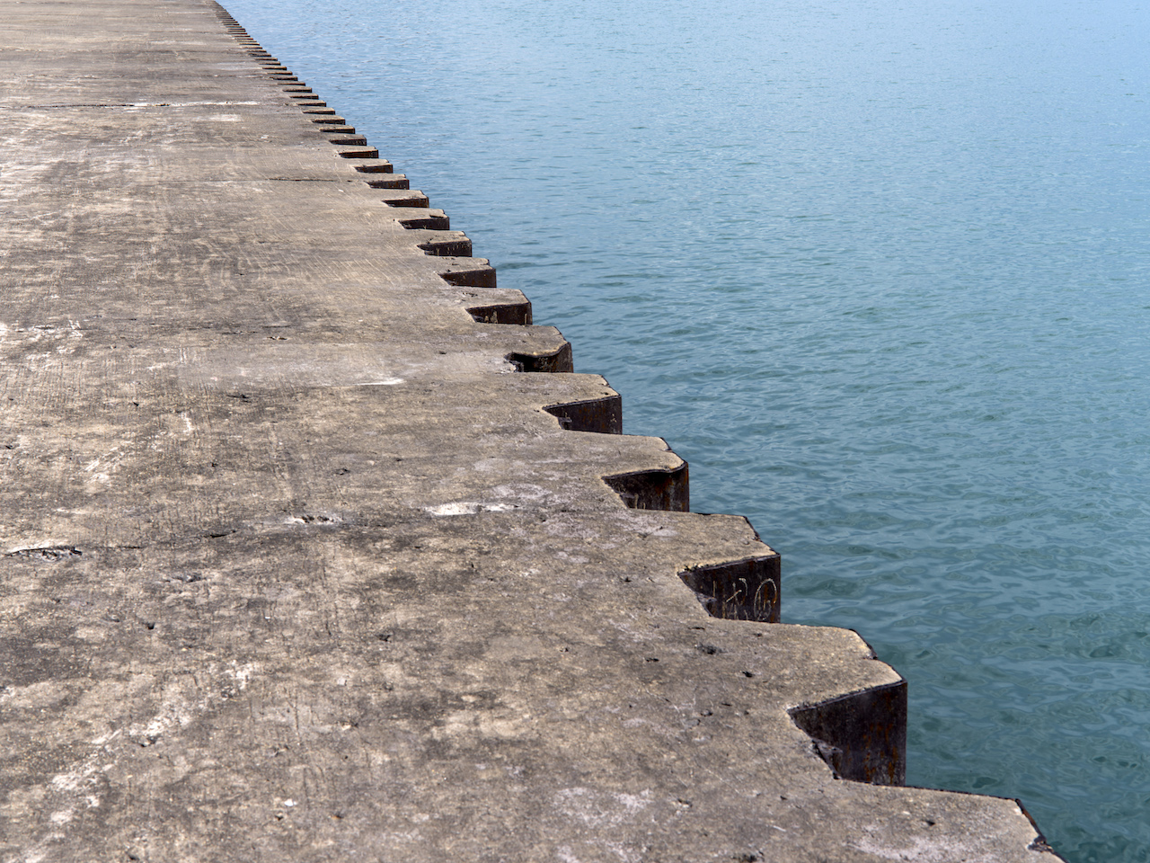 a diagonal of concrete and pilings travel diagonally with blue waters on the right side
