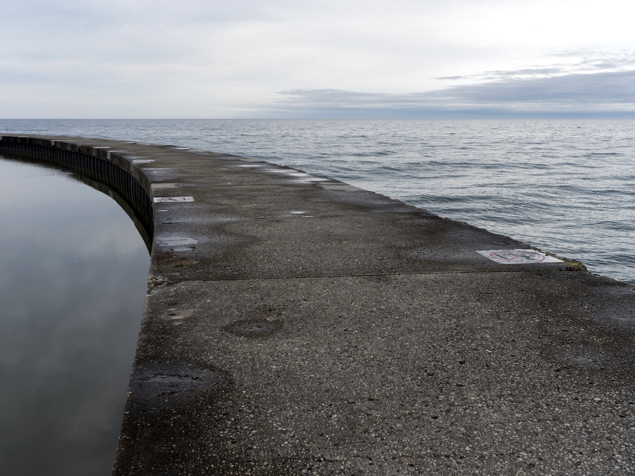 a scorpion tail of concrete curves to the left into Lake Michigan with a muted sky, from The Shore series by Lincoln Schatz