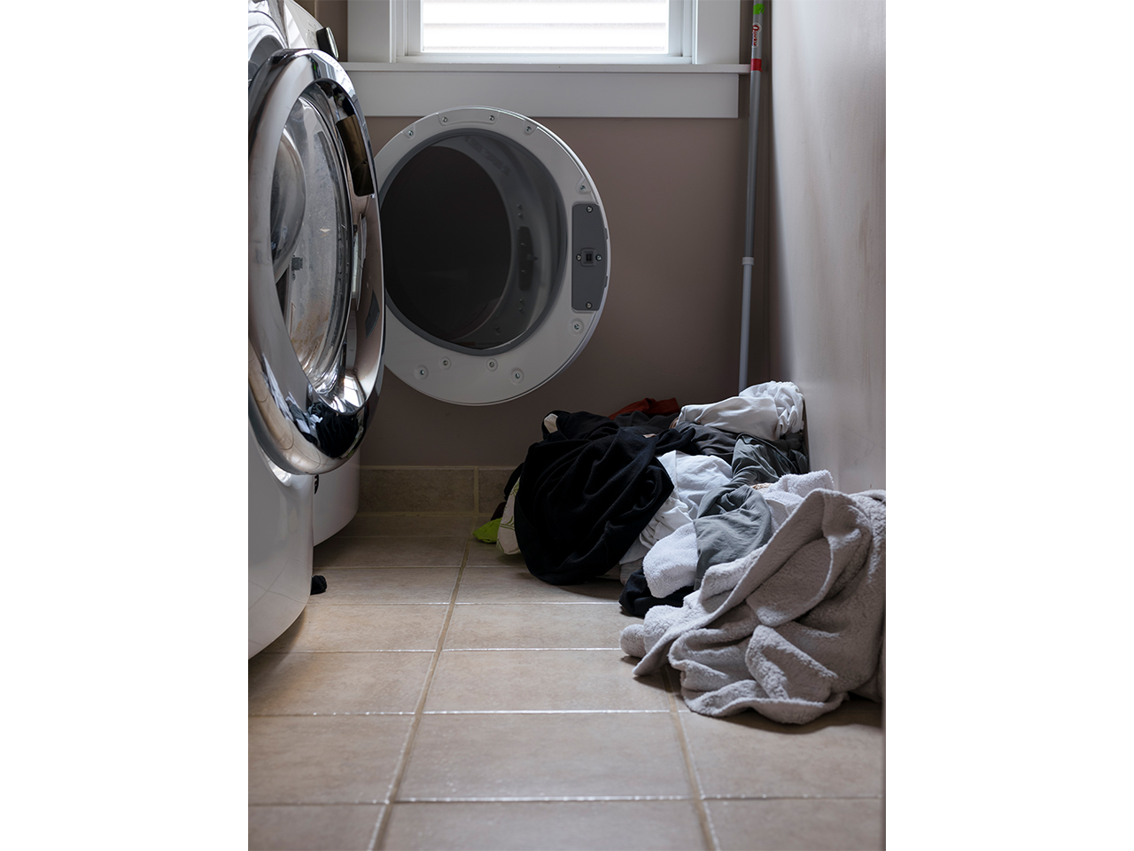 a laundry room with a washer open, clothes in a pile on the floor