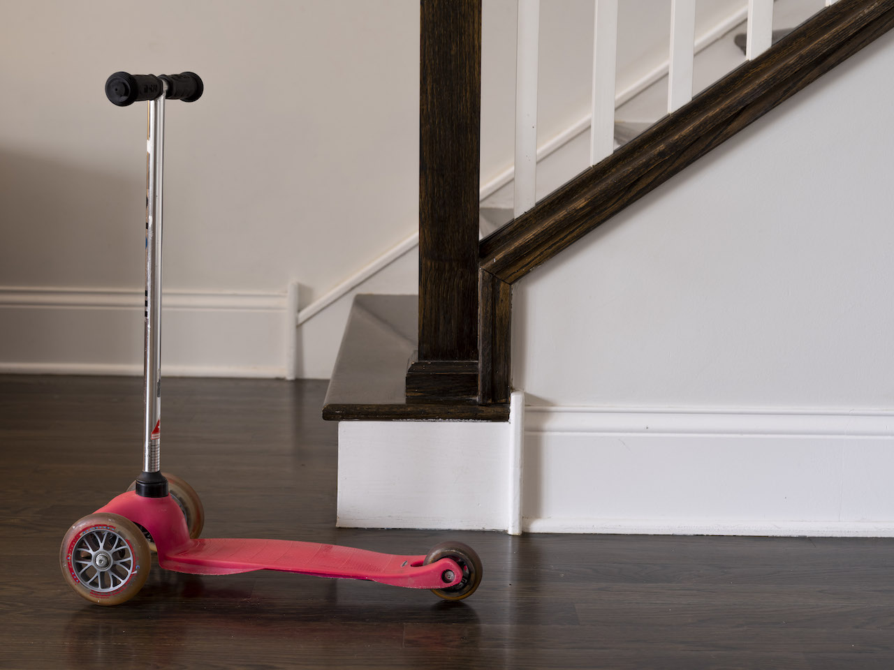 a small childrens scooter in front of a staircase in a living room