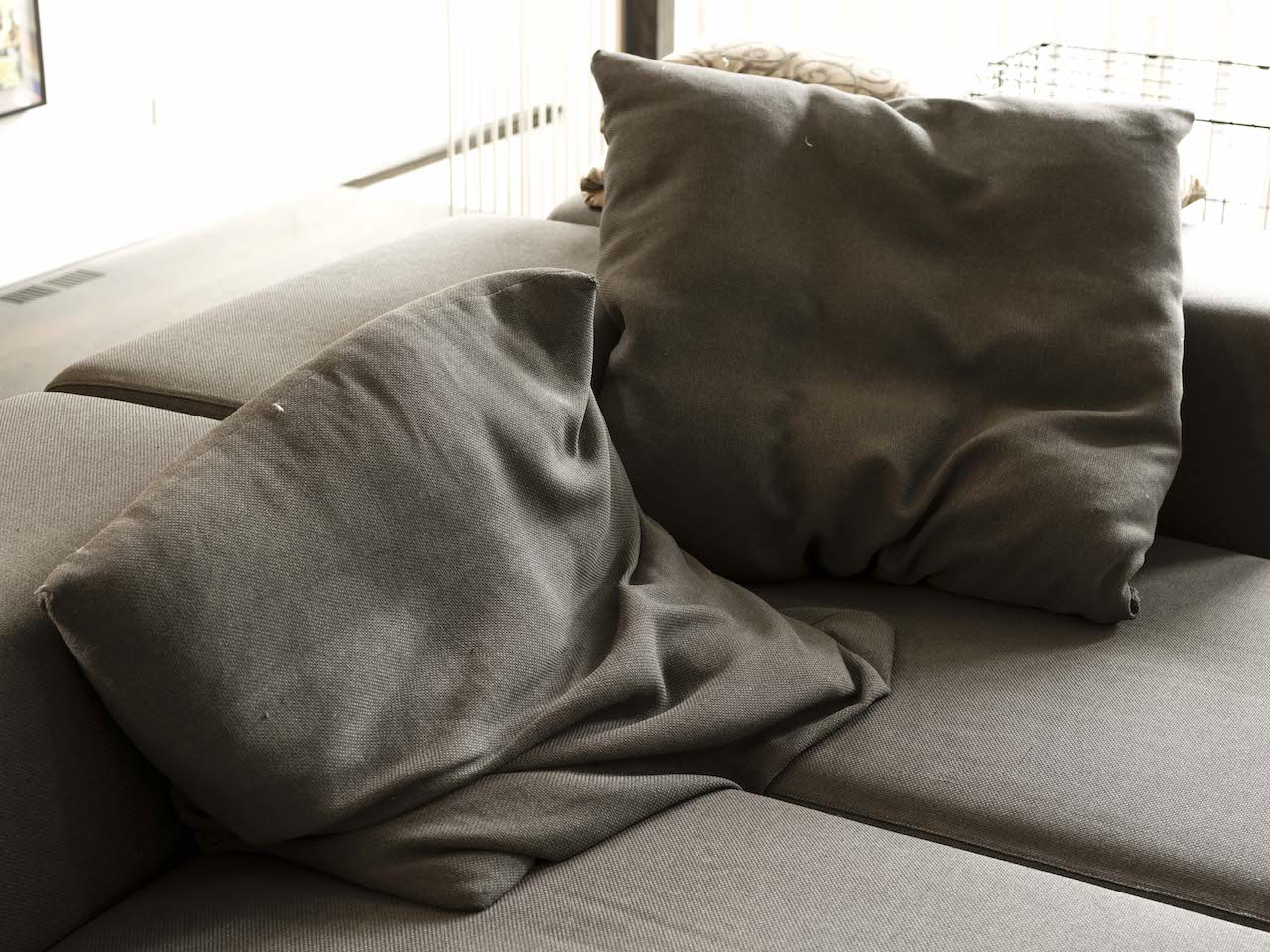 gray pillows slumped into the corner of a gray couch