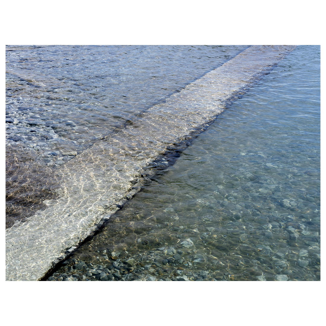 a concrete pier pushes diagonally under clear blue green waters on Lake Michigan