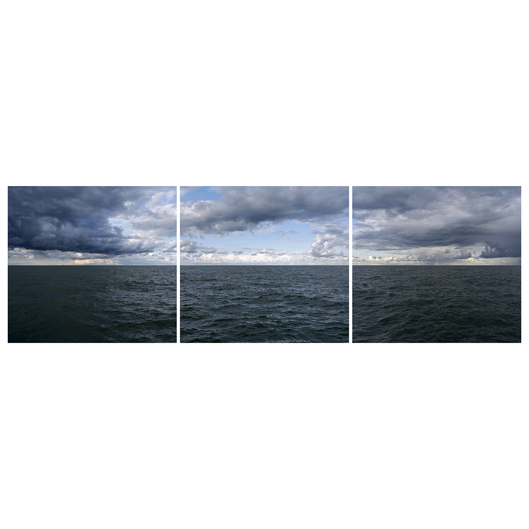 a dramatic and stormy day on Lake Michigan with a blue sky in the center and dark waters underneath