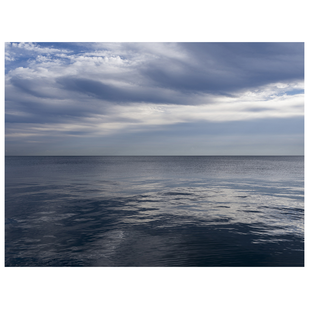 clouds sweep up into the sky like a pompadour over dark blue waters of Lake Michigan