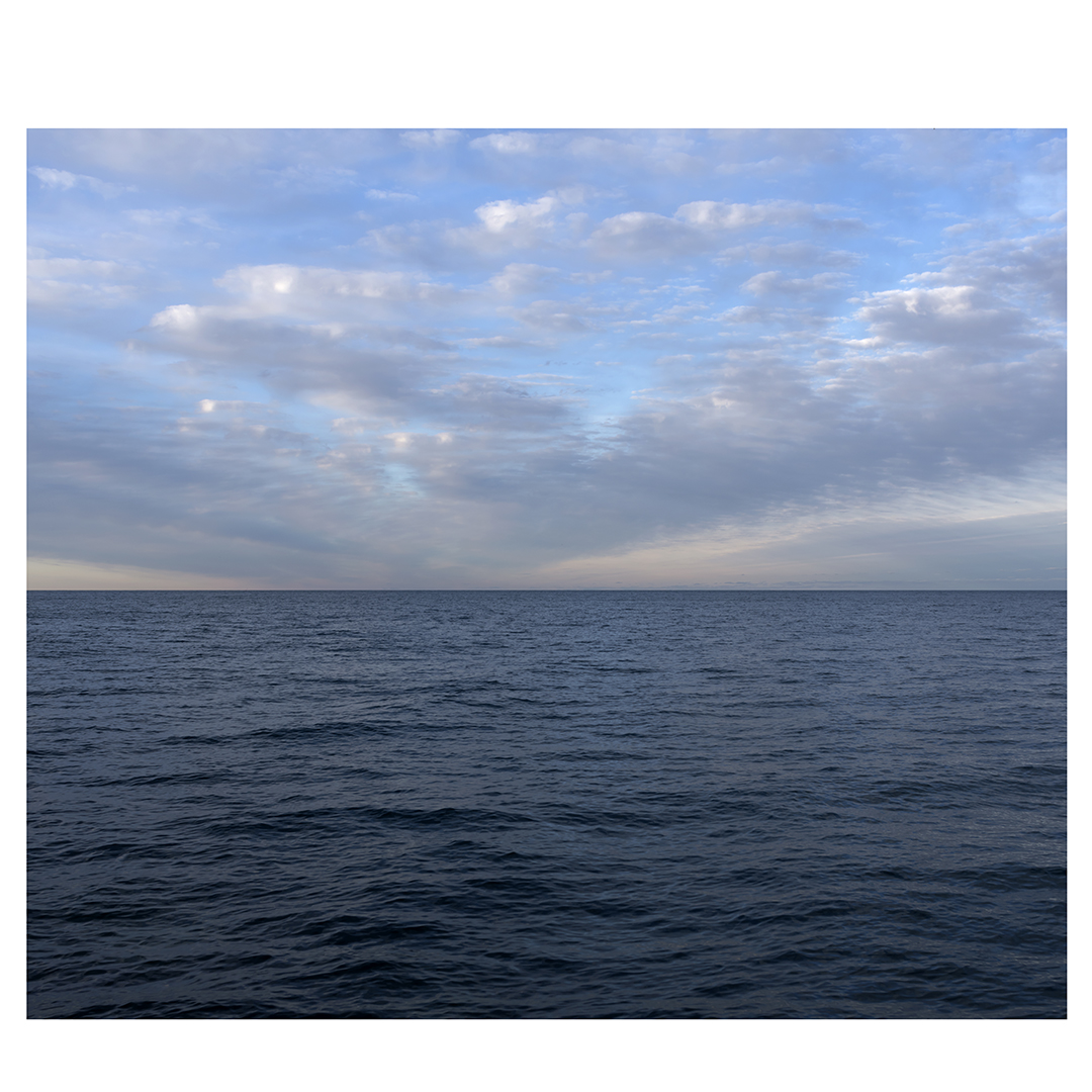 A diptych with clouds that radiate from the horizon like spokes on a bike wheel, rippling across the sky over Lake Michigan, this is the left panel.