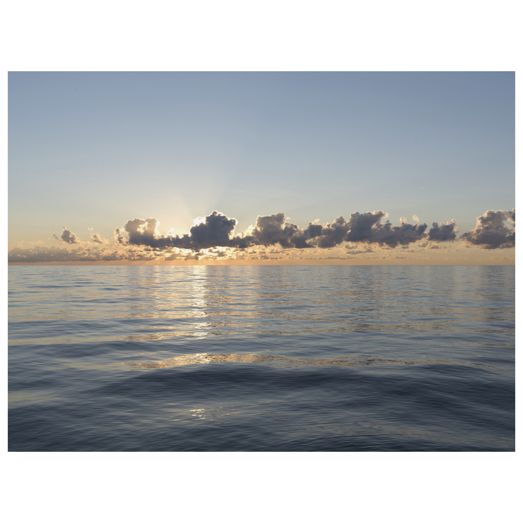 A row of clouds sits perfectly just above the horizon line, a blue to peach gradient in the sky and mirrorlike blue waters beneath
