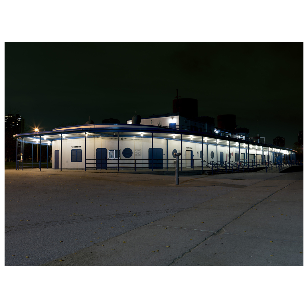 a building on the beach of Lake Michigan at night, shaped like an oval, the building is white with blue trim