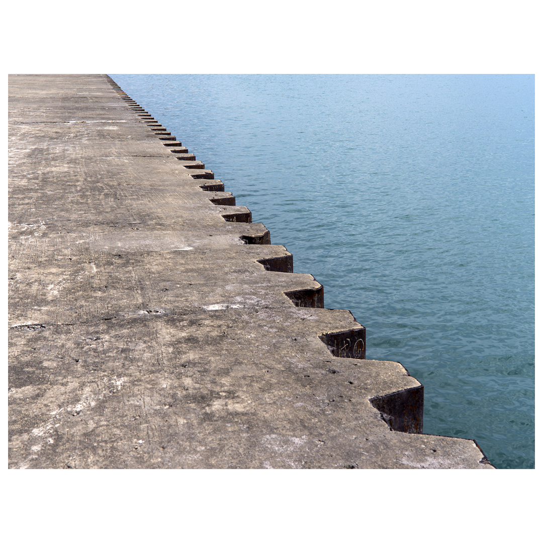 a concrete barrier cuts diagonally from right to left, a rich blue lake fills the right side, a concrete path on the left