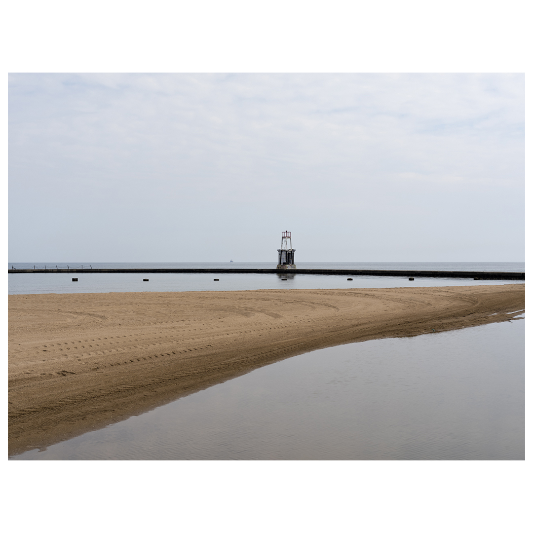 A muted morning on Lake Michigan, with clouds in the sky. A sandbank cuts from left to right in front of a concrete pier and small lighthouse
