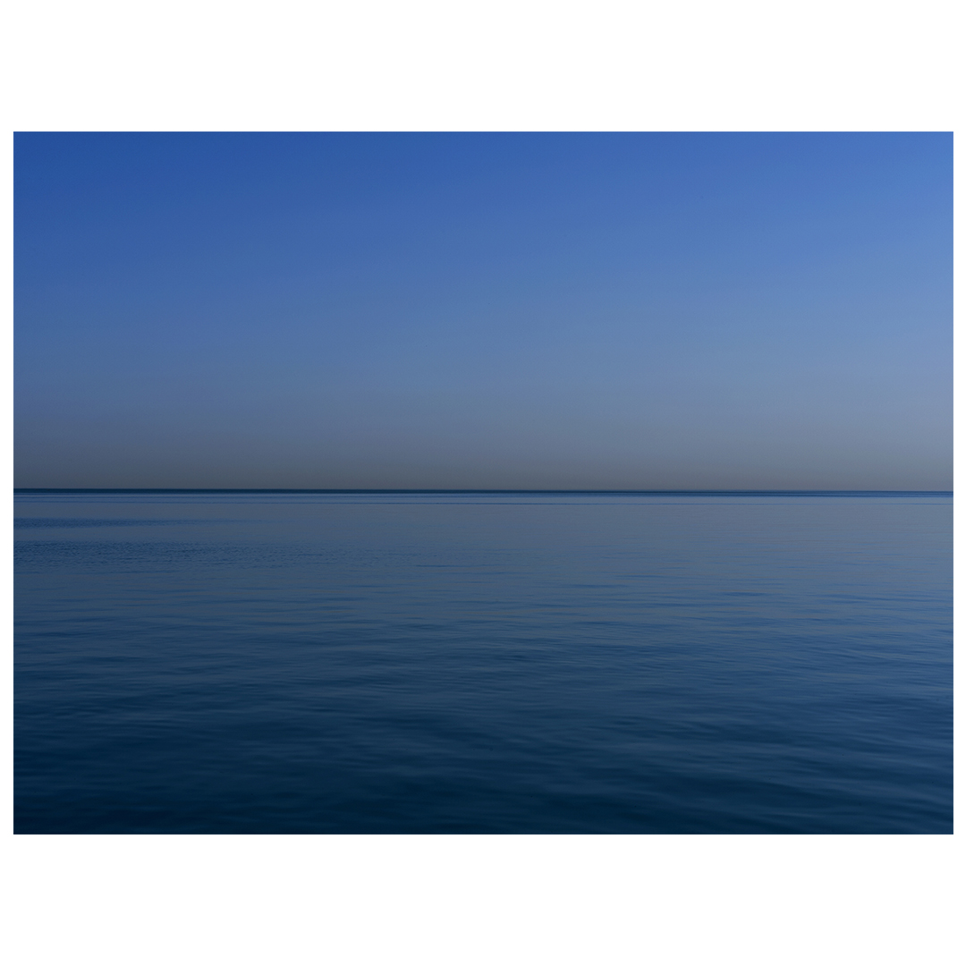 the most blue of summer days on the lake, a wisp of clouds on the right side of an otherwise still and serene day, panel 1 of 2