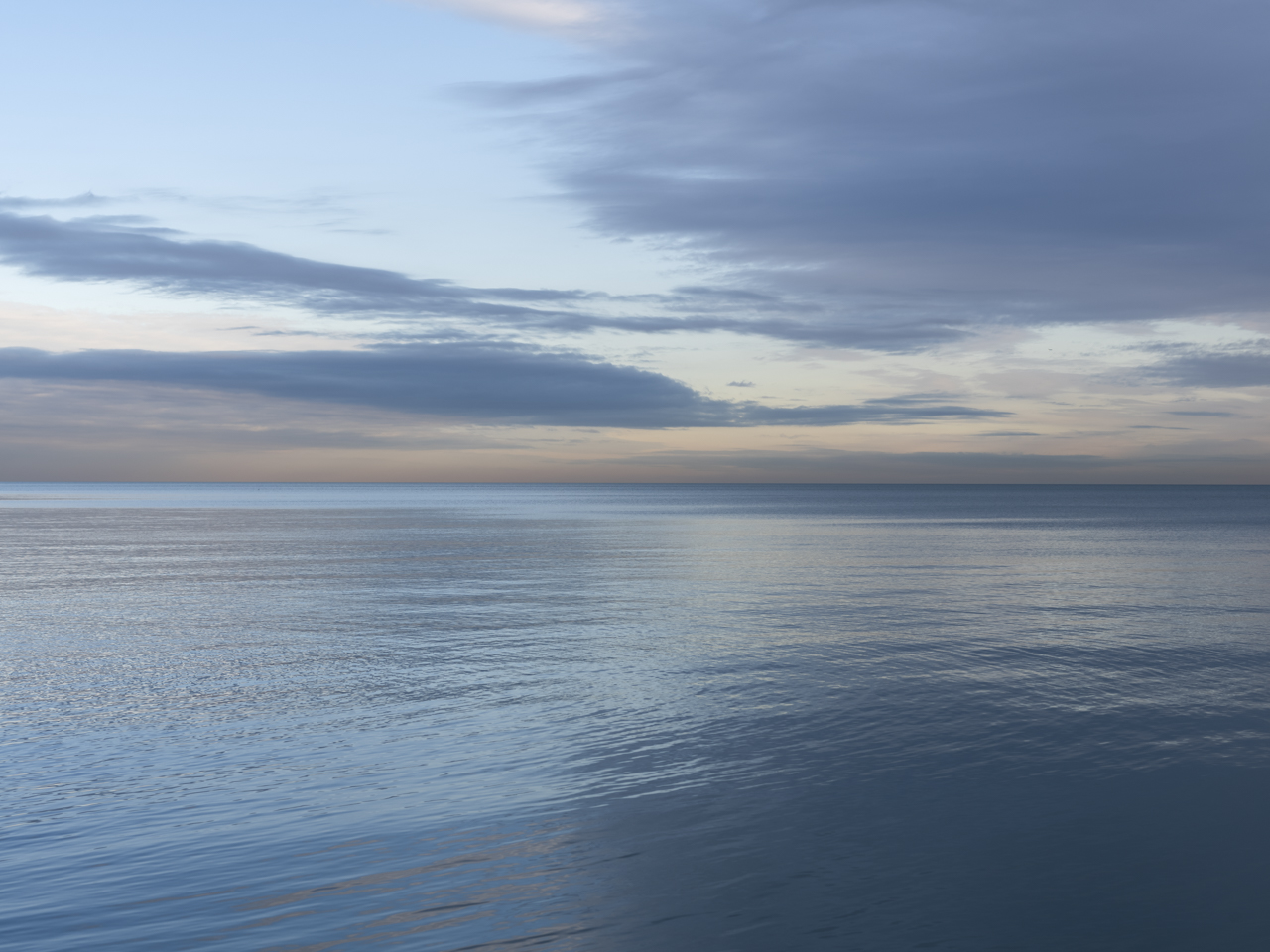 an early morning on Lake Michigan, clouds drift thinly through a blue and orange sky, a still lake surface reflecting their form and color