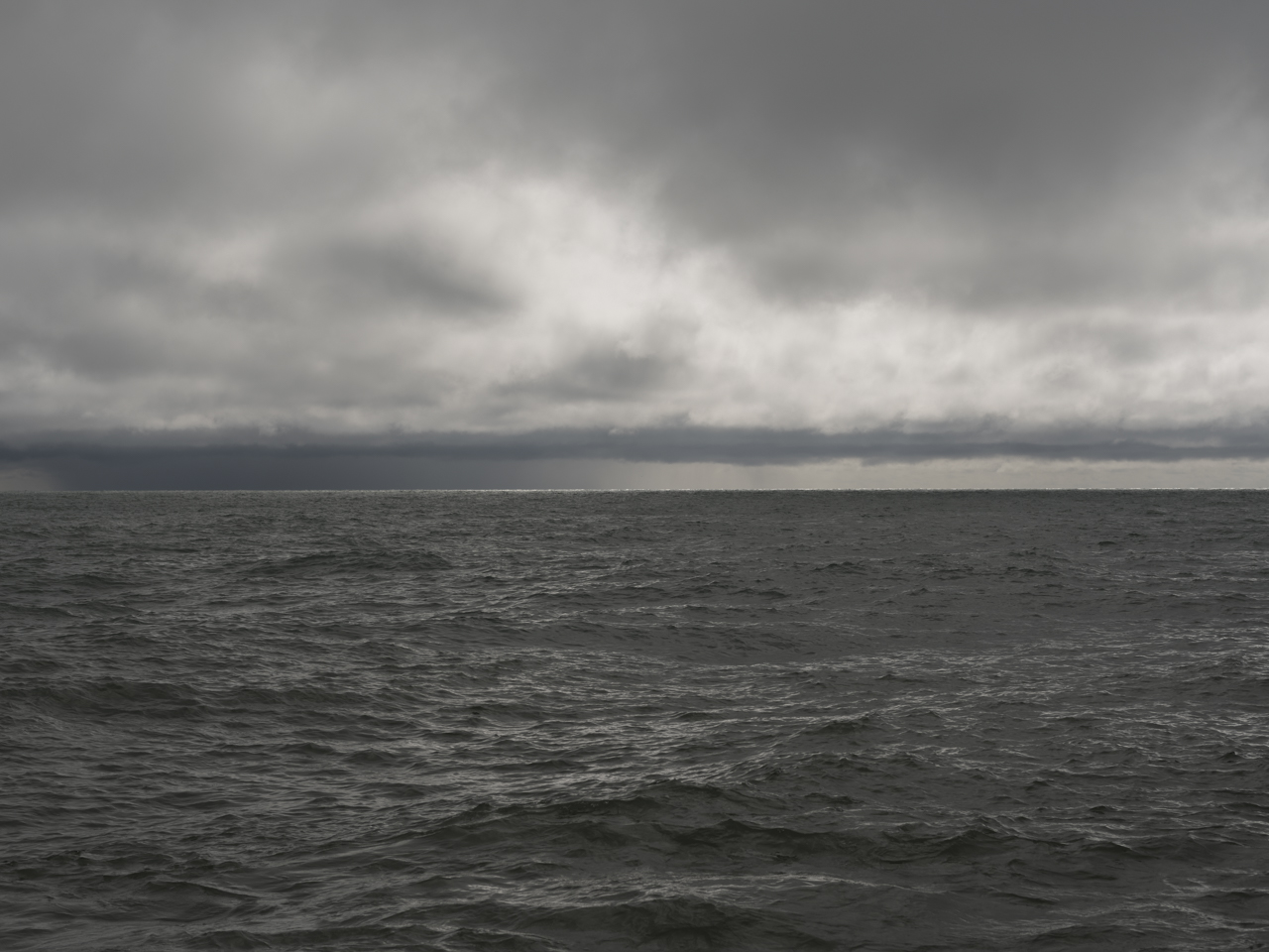 dark and deep waters are pushing against the shore while heavy clouds fill the sky
