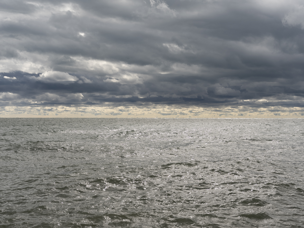stormy and dark blue and black clouds sit heavily in the sky over bronze and green-gray waters