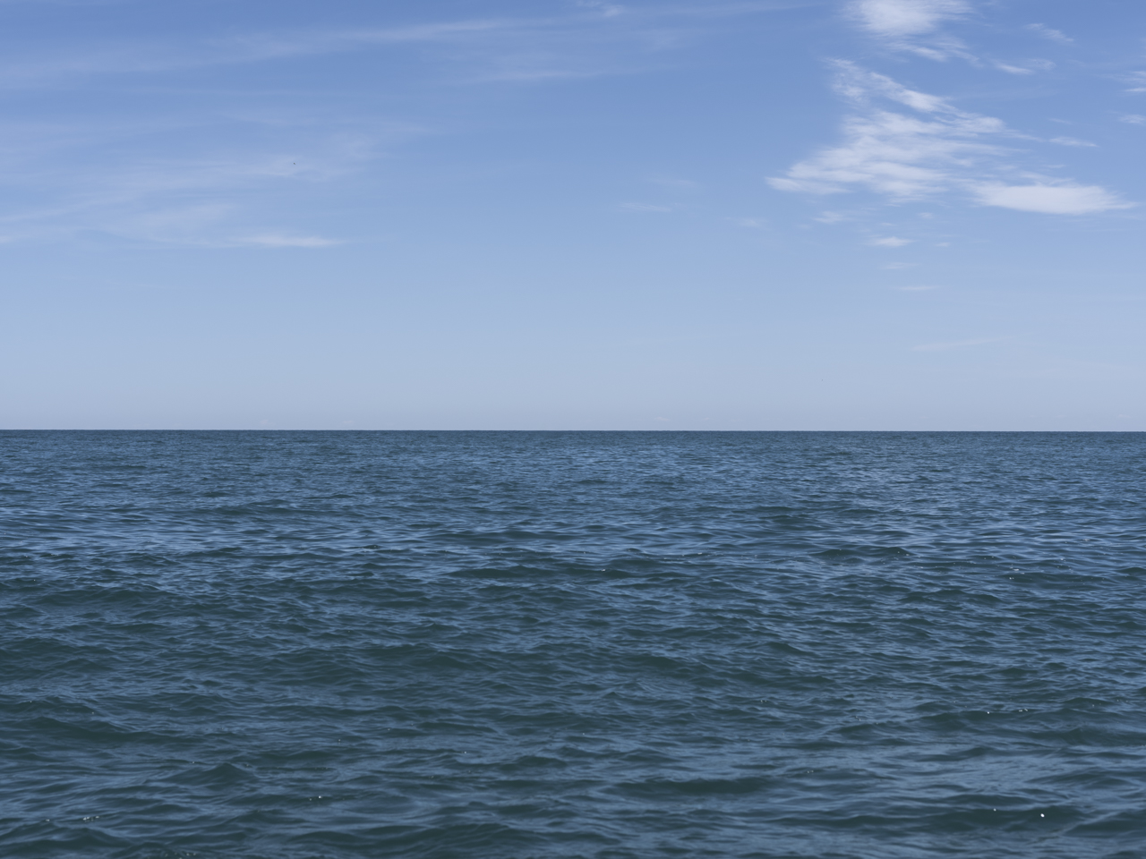 wisps of clouds sit high in the sky on another perfectly beautiful blue day on Lake Michigan