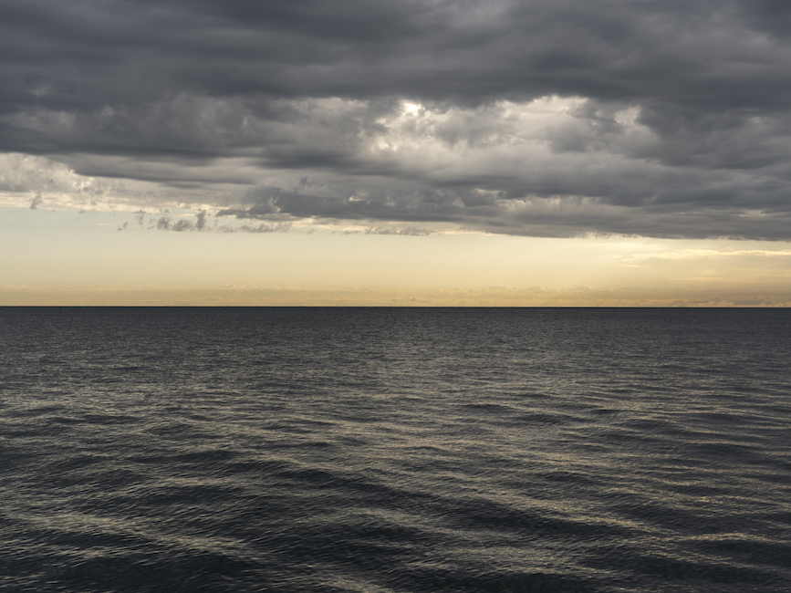a yellowish day on Lake Michigan where the lake water is black in color and textured heavily with dark gray clouds in the sky