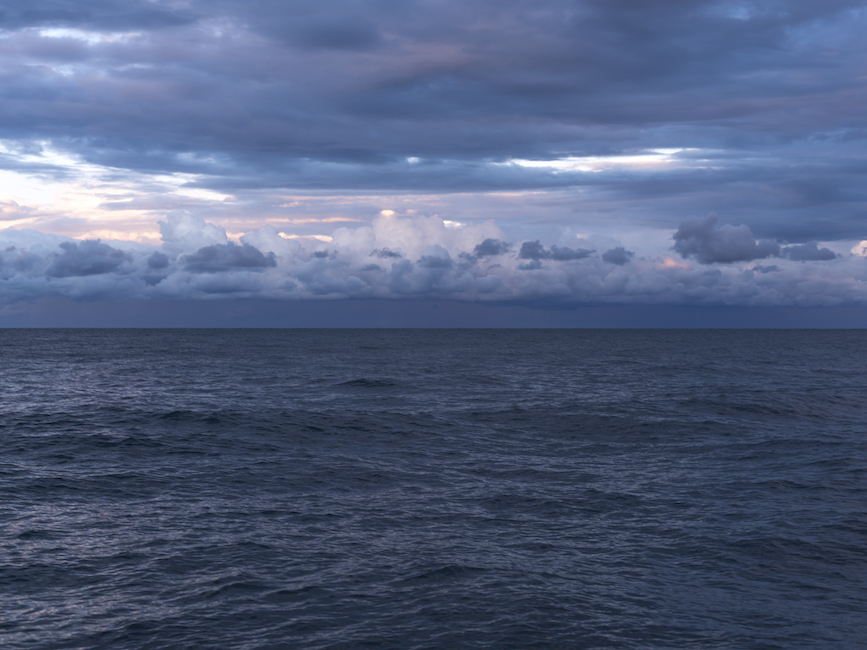beautiful clouds, purple, blue and pink sit heavily in the sky over a dark blue Lake Michigan