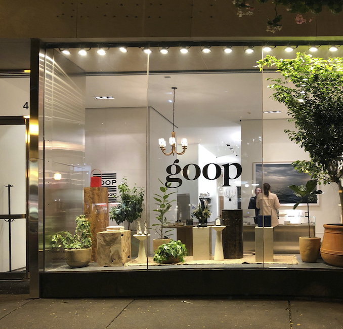 the Goop Chicago storefront is lit from within with a framed print by Lincoln Schatz hanging behind the front counter of the Sasha Adler designed store