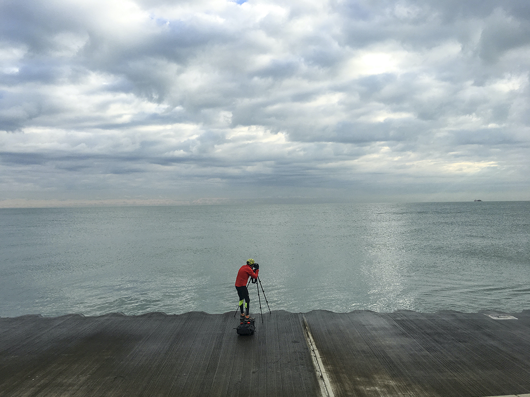 Lincoln Schatz stands on a concrete wall in front of Lake Michigan taking pictures with his camera