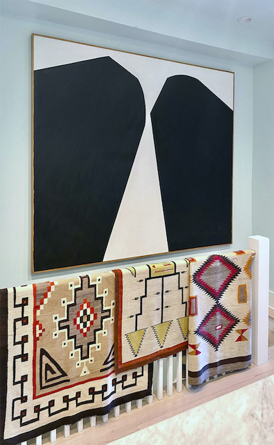 large scale oil stick on canvas painting with black abstract shapes and a white background hangs above a stairwell that has a bannister draped with three floor rugs by Todd Schwebel