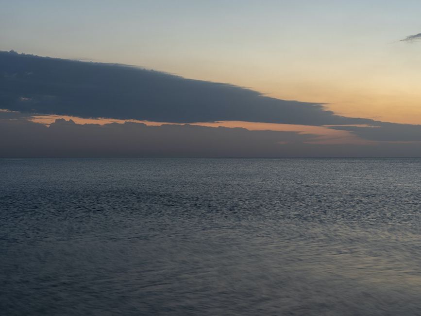 dark blue clouds appear flat in an ombre orange to light blue sky, early in the morning on Lake Michigan, which appears darkly lit with little wind on the surface of the lake water