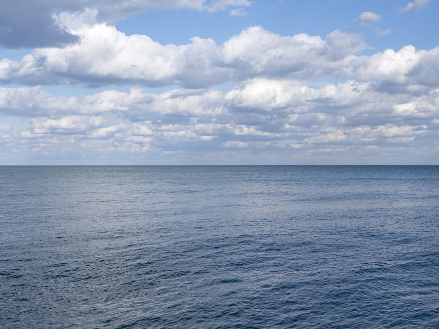 a light blue lake with puffy white clouds overhead in a perfect blue sky, the clouds are reflected in the rippling surface of Lake Michigan