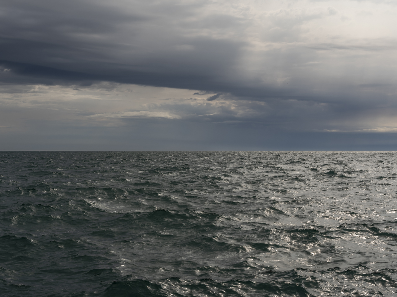 a stormy day on Lake Michigan where the clouds are breaking and forming in the sky while pouring rain out over the horizon, the lake a dark green blue and roiling below the sky
