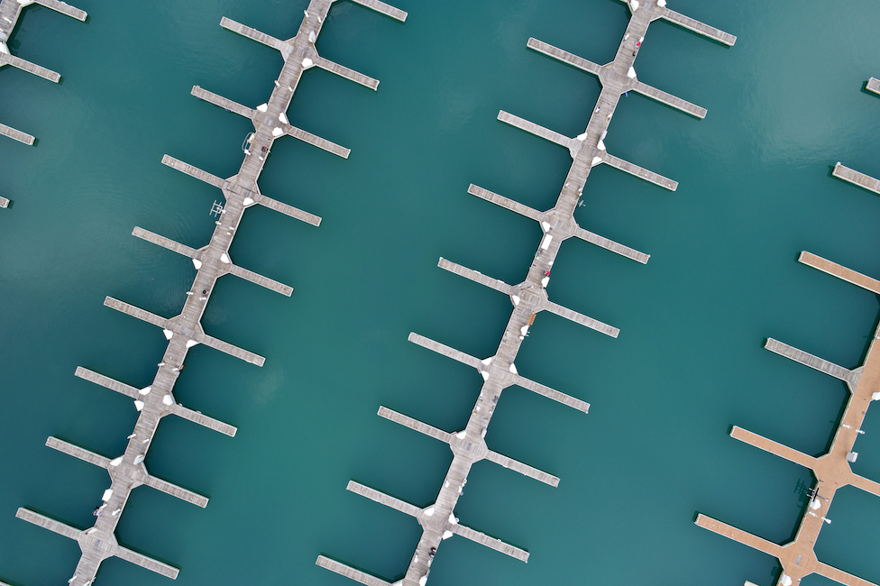 an aerial photo from a drone taken of the Diversey Harbor boat docks on Lake Michigan at the end of season, 4 boat docks cut through the photo from right to left