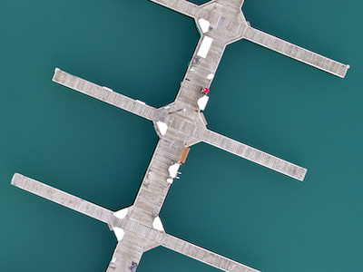 a detail from an an aerial photo from a drone taken of the Diversey Harbor boat docks at the end of season, 4 boat docks cut through the photo