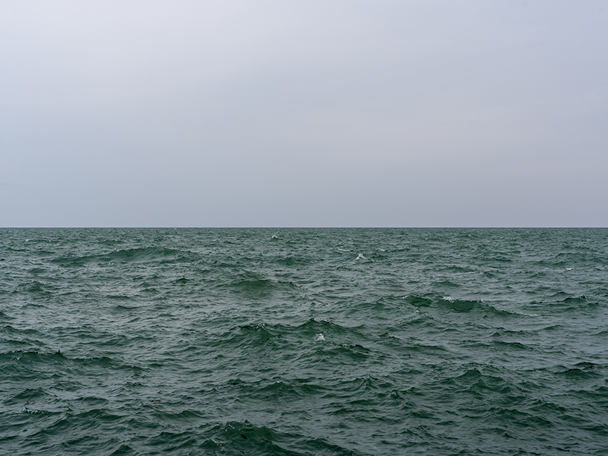 the emerald green waters of lake michigan are pushed into peaks by wind while a blank gray sky looks overhead