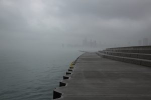 a foggy Chicago skyline from early in the morning when a large storm is sitting overhead, a concrete wall and steps sit on the right side of this photo